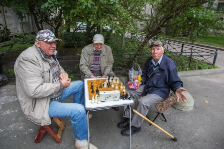 Pensioners play chess in the courtyard