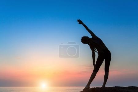 Photo for Silhouette of the woman on the sea beach performing gymnastic exercises at sunrise. - Royalty Free Image