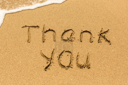 Thank you drawn on the sea sand with the soft wave.