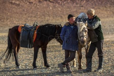 SAGSAY, MONGOLIA - SEP 28, 2017: Young men Eagle Hunters standing near their horses during hunting in the mountain desert of Western Mongolia.