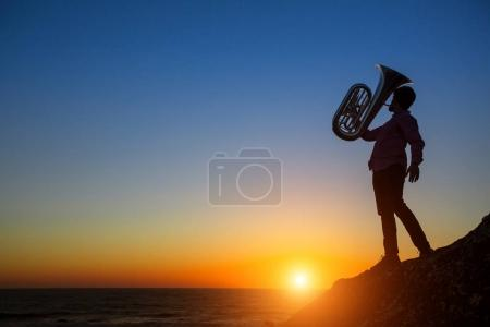 Silhouette of a musician play Tuba at sunset on sea shore.