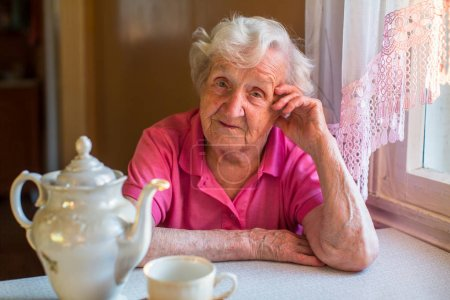 Portrait of an elderly woman behind a dining table.