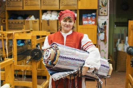 "VAZHINY, LENINGRAD REGION, RUSSIA - DEC 21, 2017: Weaver in the Textile Studio of decorative art ""Tekstilnaya Plastika"", at municipal budgetary institution of culture."