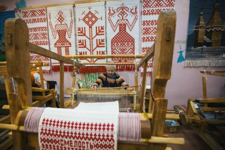 "VAZHINY, LENINGRAD REGION, RUSSIA - DEC 21, 2017: Weaver while working in the Textile Studio of decorative art ""Tekstilnaya Plastika"", at municipal budgetary institution of culture."