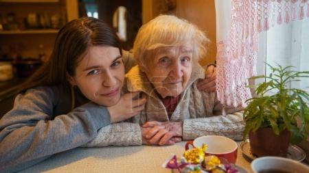Portrait of  elderly woman with her adult granddaughter.