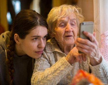 elderly woman with adult granddaughter looks at a smartphone