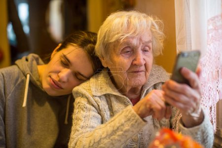 Elderly woman looks at a smartphone, with his adult granddaughter.