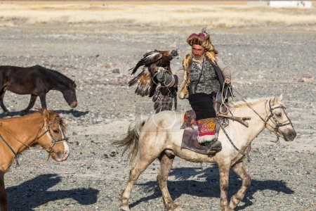 SAGSAY, MONGOLIA - SEP 28, 2017: Eagle Hunter traditional clothing, while hunting to the hare holding a golden eagles on his arms in desert mountain of Western Mongolia.
