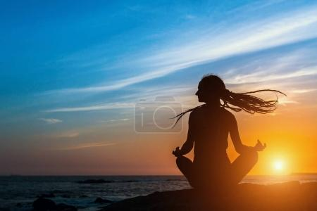 Yoga silhouette meditation woman on the ocean during amazing sunset.
