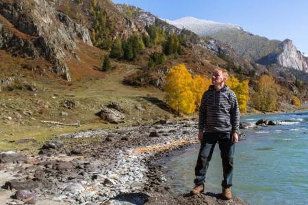 Man stands on the Bank of the Katun river in the Altai mountains, Russia.