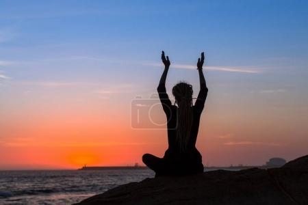 Silhouette of yoga meditation woman on the ocean during amazing sunset.