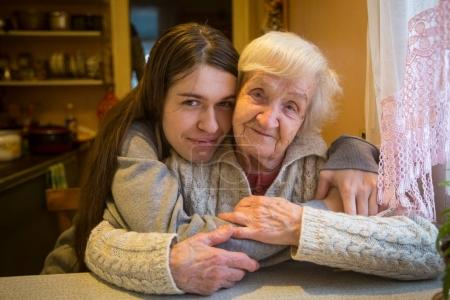 An elderly woman in an embrace with an adult granddaughter posing for the camera in a village house.