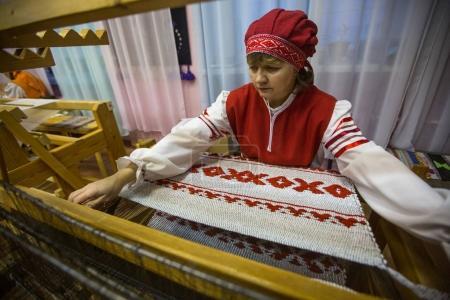 "VAZHINY, LENINGRAD REGION, RUSSIA - DEC 21, 2017: Weaver while working in the Textile Studio of decorative art ""Tekstilnaya Plastika"", at municipal budgetary institution of culture."