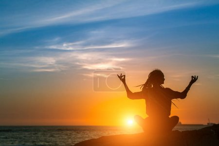 Yoga woman silhouette. Meditation on the Ocean during amazing sunset. Healthy lifestyle.