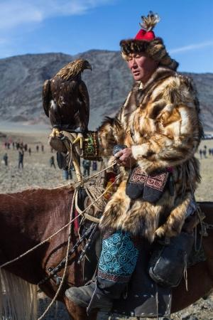 """OLGIY, MONGOLIA - SEP 30, 2017: Kazakh Eagle Hunter traditional clothing, with a golden eagle during annual national competition with birds of prey """"Berkutchi"""" of Western Mongolia."""