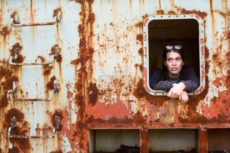 Portrait of a young woman in the window of an abandoned iron rusty object.