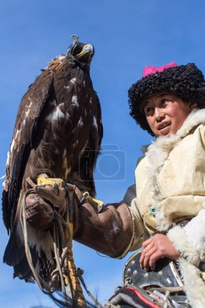 BAYAN-ULGII, MONGOLIA - SEP 30, 2017: Eagle Hunter at traditional clothing, while hunting to the hare holding a golden eagle, in mountains western Mongolia.