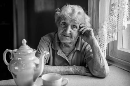 Portrait of elderly woman drinking tea at table.