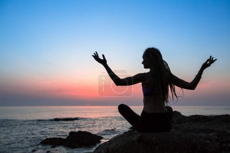 Yoga meditation woman silhouette on the Sea during amazing sunset.