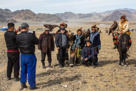 "OLGIY, MONGOLIA - SEP 30, 2017: Eagle Hunters at traditional clothing, with a golden eagle on his arm during annual national competition with birds of prey ""Berkutchi"" of West Mongolia."