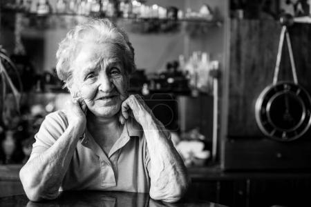 Portrait of an elderly woman at the table in the house.