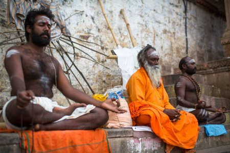 VARANASI, INDIA - MAR 15, 2018: Sadhu (holy man) on the Dashashwamedh Ghat of Ganga river. Varanasi is most important pilgrimage sites in India, one of the 7 sacred cities of Hinduism.