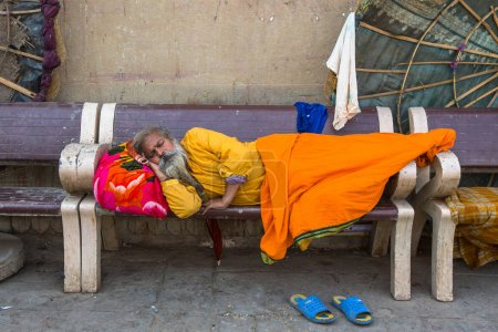 VARANASI, INDIA - MAR 16, 2018: Hindu sadhu on the ghats of the Ganges river. According to legends, the city was founded by God Shiva about 5000 years ago.