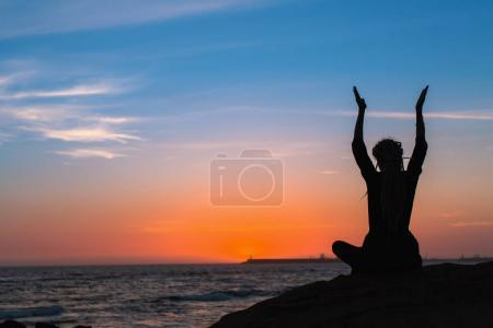 Meditation woman yoga silhouette. Sea during amazing sunset. Fitness and healthy lifestyle.