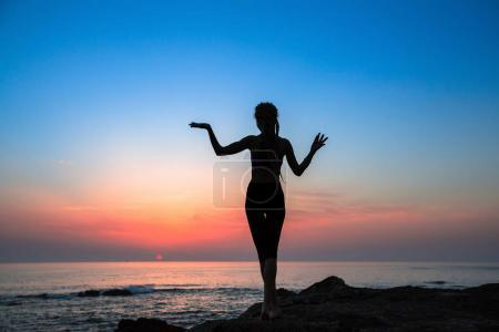 Fitness woman silhouette on the sea during amazing sunset.  Healthy lifestyle.