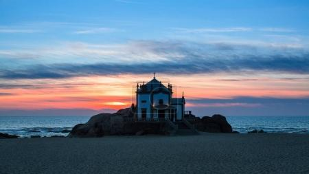 Chapel Senhor da Pedra at sunset, Miramar Beach in Porto, Portugal.