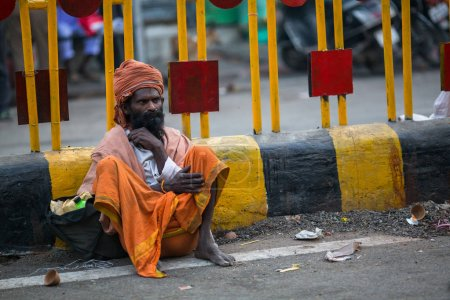 VARANASI, INDIA - MAR 23, 2018: Indian beggar sitting on the street. According to legends, the city was founded by God Shiva about 5000 years ago.