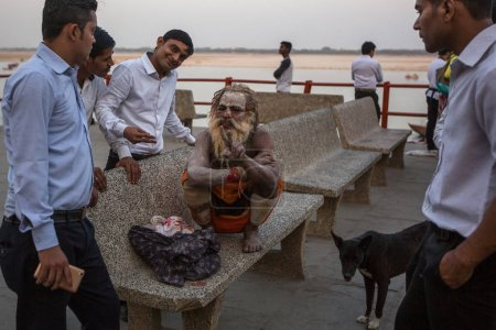 VARANASI, INDIA - MAR 26, 2018: Sadhu or Baba (holy man) on the ghats of Ganges river. Normally a sadhu is a monk, renounced, renounced material enjoyment. In India from 4 to 5 million sadhu.