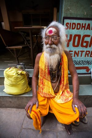 VARANASI, INDIA - MAR 27, 2018: Sadhu or Baba (holy man) on the ghats of Ganges river. Normally a sadhu is a monk, renounced, renounced material enjoyment. In India from 4 to 5 million sadhu.