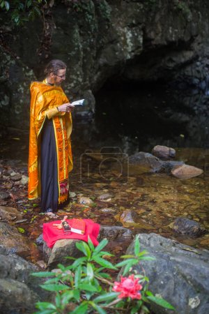 Photo for KOH CHANG, THAILAND - MAR 9, 2018: Orthodox priest during sacrament of spiritual birth - Baptism. There are currently 10 Orthodox parishes in Thailand, Orthodoxy is practiced by 0.002% of population. - Royalty Free Image