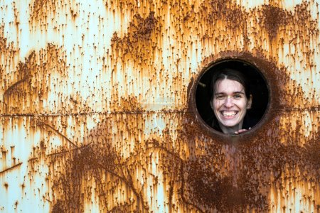 Young woman joyfully looks out of the window of an abandoned bunker.