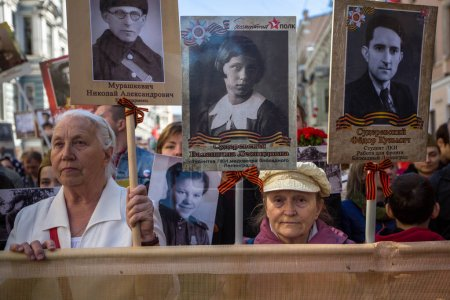 ST. PETERSBURG, RUSSIA - MAY 9, 2018: People hold flags and pictures of World War Two soldiers as they take part in the Immortal Regiment march during the Victory Day celebrations.