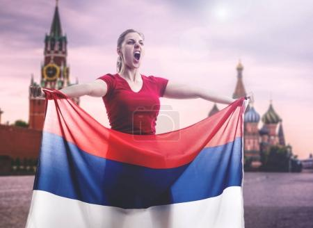 excited female fan holding national flag of Russia in Moscow