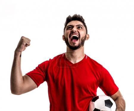 excited football player in red uniform celebrating on white background. Isolated view of cheerful male fan with soccer ball