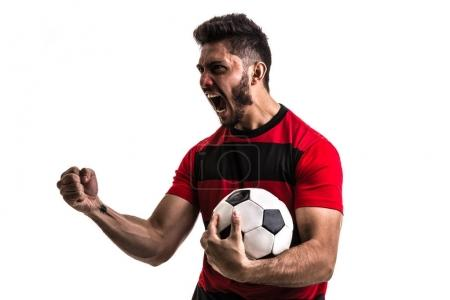 excited sportsman in red and black uniform on white background. Isolated view of male fan holding soccer ball
