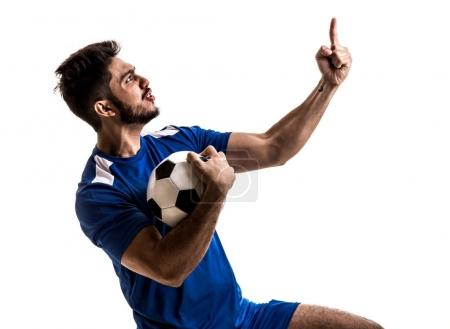 excited football player in blue uniform celebrating on white background. Isolated view of cheerful male fan with soccer ball and pointing finger