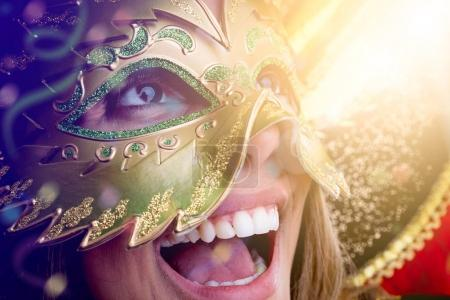 happy young woman wearing carnival costume and mask