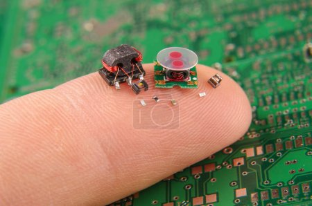 Photo for Modern electronics surface mount components in comparison to human finger - Royalty Free Image