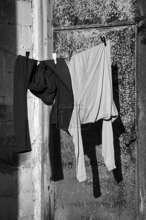 Male clothes hanging to dry outdoor of house. Rusty closed door and cement brick wall at background. Black and white