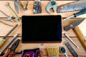 Tablet and old tools on a natural wooden background.