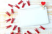 Love card concept. Clothespin with heart on a white wooden background. Valentines day.