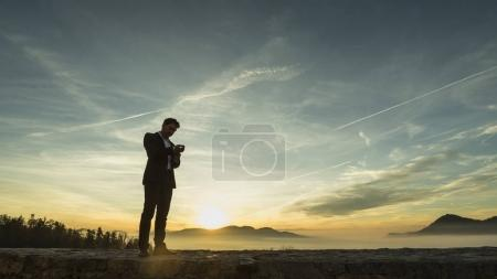 Businessman standing outdoors  fixing his suit against a colorfu