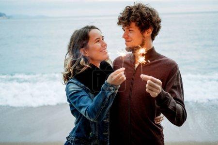 Photo pour Souriant jeune beau couple heureux tenant scintille contre la mer . - image libre de droit