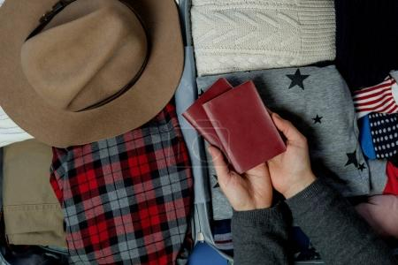 Photo for Travel board in Open suitcase packed with clothes. Summer vacations. Top view - Royalty Free Image