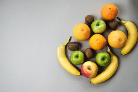 Photo for Colorful fresh fruit on Gray table. Orange, banana, apples, kiwi, grapefruit. Flat lay, top view, copy space. Fruit background. - Royalty Free Image