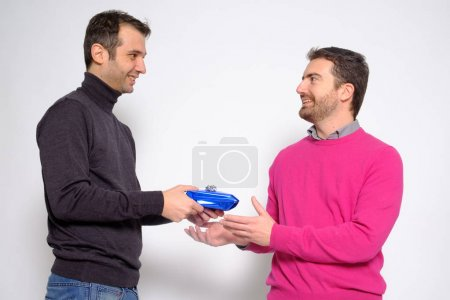 Portrait of a men gay couple in studio exchanging a present